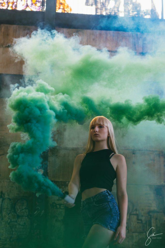 Lány kézi füstbombával. Füstbombás fotózás. Zöld füstbomba. Modell fotózás.